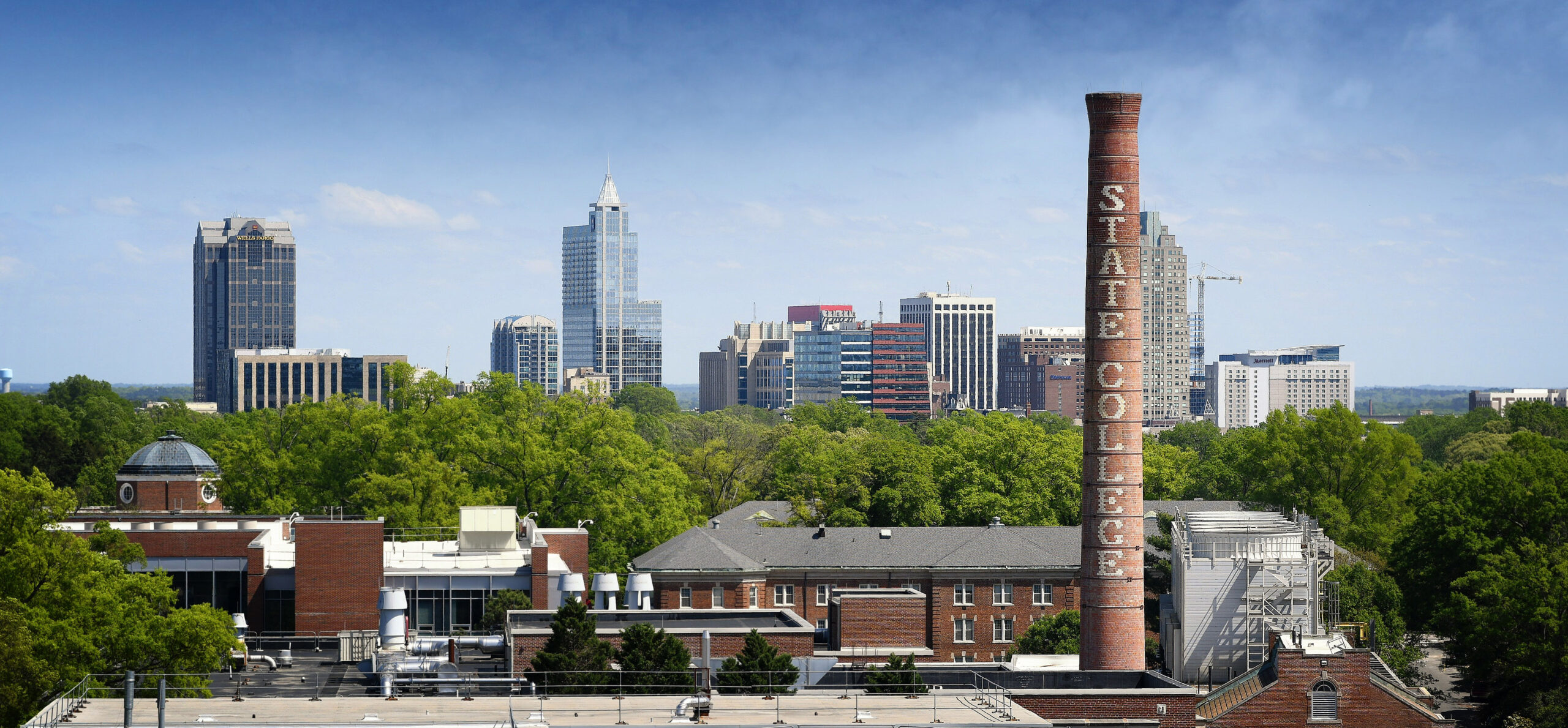 Downtown Raleigh skyline, framed by the State College smoke stack.