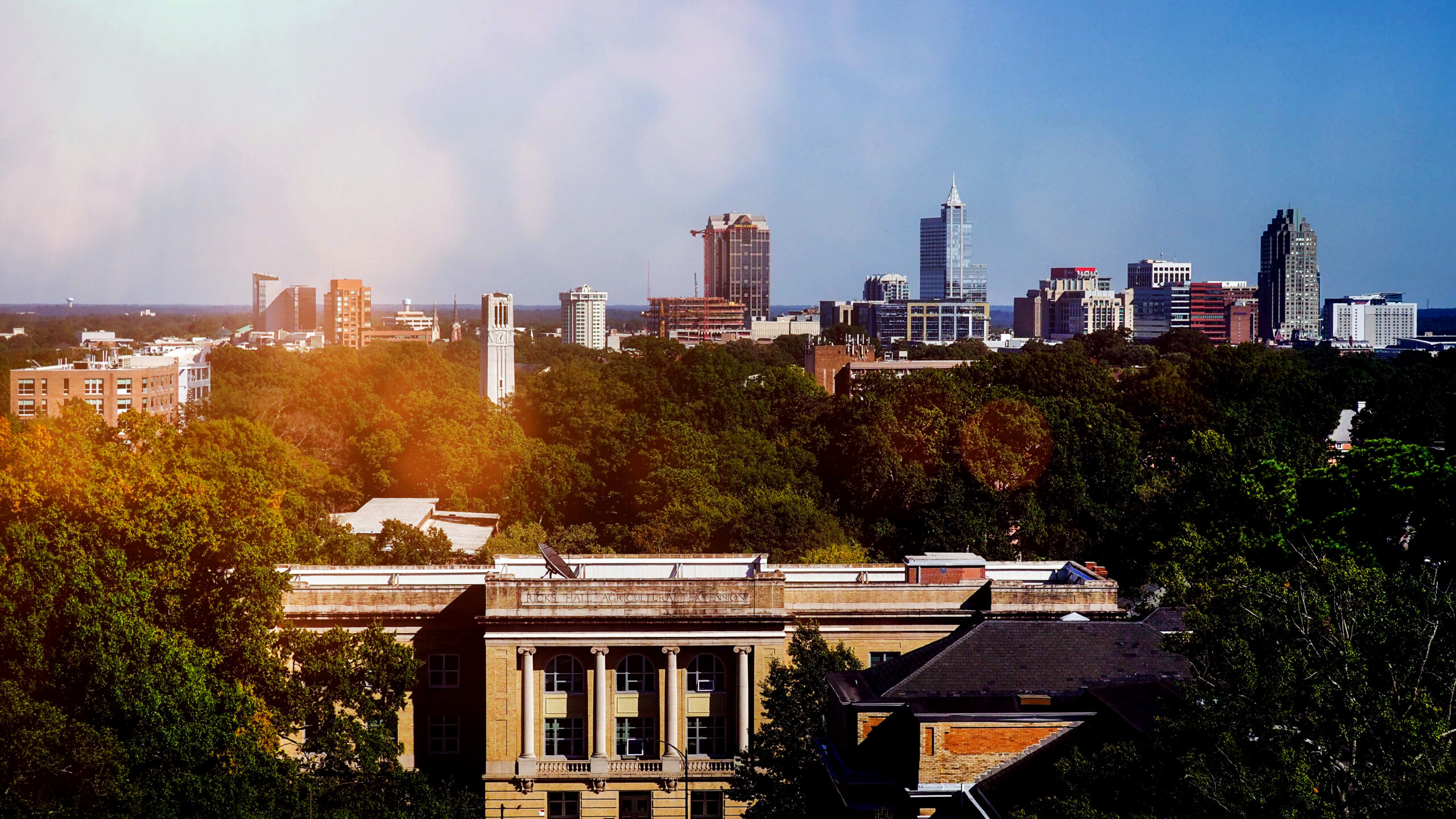 Ricks Hall (in the foreground) and the Belltower on NC State's campus, with downtown Raleigh behind.