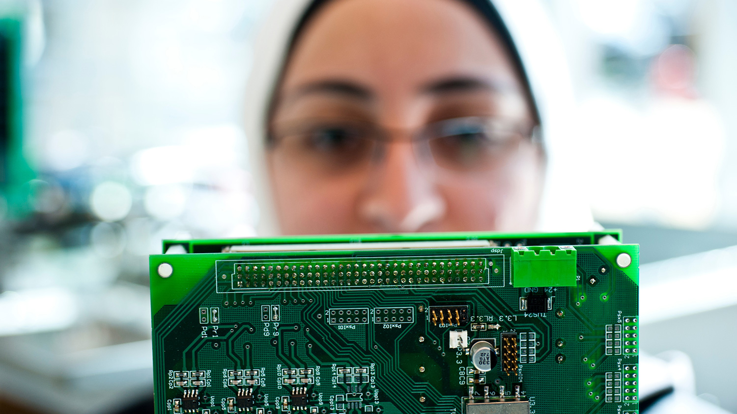 A woman examines a large block of electrical chips.